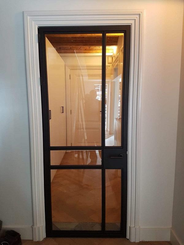 Stalen scharnierdeur met glas in hout kozijn